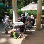senioři sedící pod deštníkem