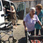 uživatelka s chodítkem a sociální pracovnice pomáhajicí seniorům z auta